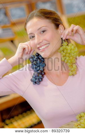 Funny woman holding grapes as earrings