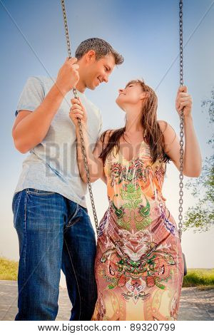 swinging younger adult outdoors smiling