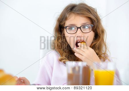 Little girl having her breakfast in the kitchen