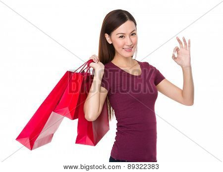 Young woman with shopping bag and ok gesture