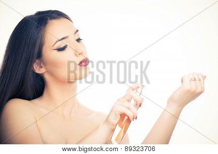 Beautiful brunette girl applying perfume on her hand
