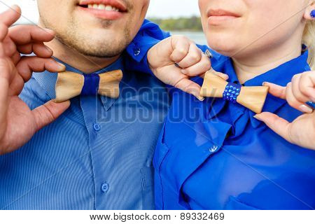 Man And Woman In Blue Shirts With Wooden Bow Tie