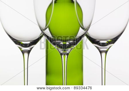 Three Empty Glasses Of Wine And Green Bottle