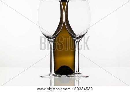 Two Empty Glasses Of Wine And Brown Bottle
