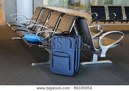 Blue suitcase at an airport lobby with chairs.