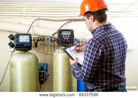 Worker Checking Work Of Industrial Equipment On Factory