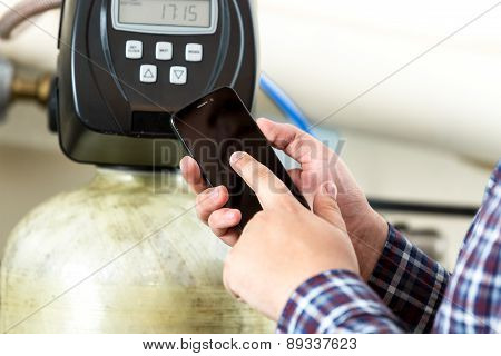 Man Typing Factory Equipment Meter Reading At Smartphone