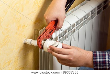 Closeup Of Man Installing Heating Radiator And Connecting Valve