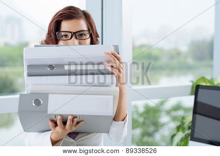 Assistant with a stack of binders