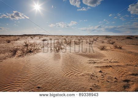 Desert Under A Blue Sky With Clouds