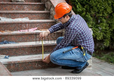 Builder Checking Stairs Height By Measuring Tape