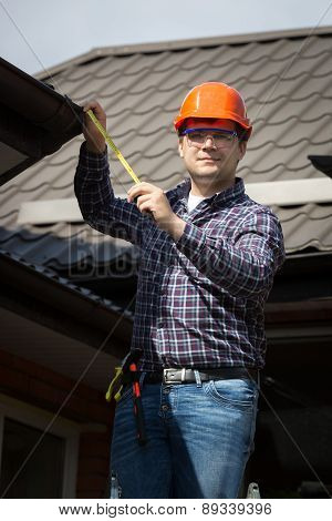 Worker In Hard Hat Measuring Size Of House Roof