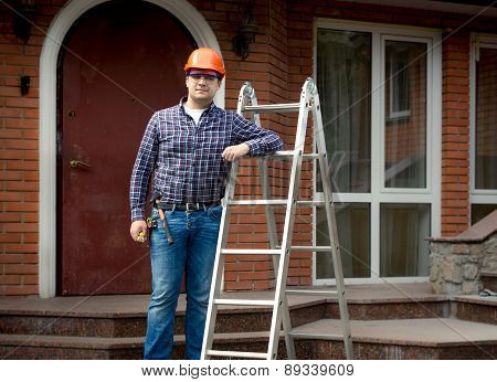 Worker Posing With Metal Ladder Against Building House