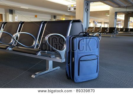 Blue suitcase at airport gate with chairs.