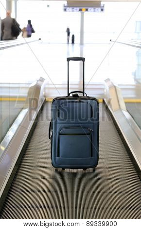Blue suitcase on conveyor belt at an airport.