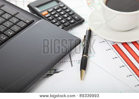 Calculator And Cup Of Coffee On The Financial Documents