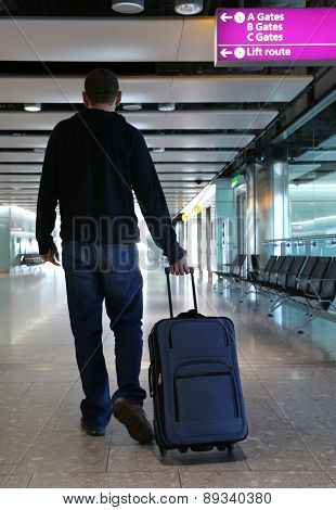 Man walking with suitcase at an airport.