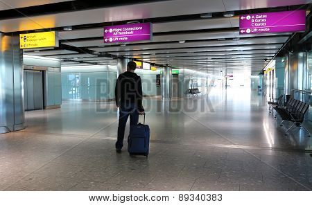 Man with suitcase at an airport lobby.