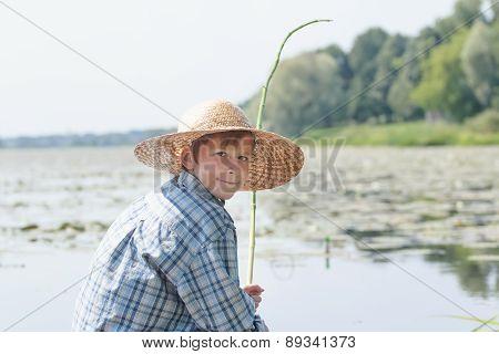 Angling Teenage Boy With Handmade Green Twig Fishing Rod Is Looking Back