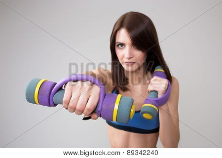 athletic woman pumping up muscles with dumbbells