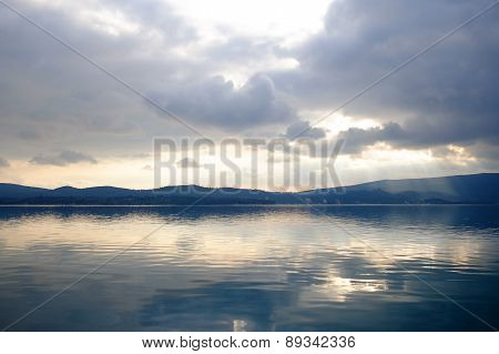 Sunset With Clouds Reflected In The Calm Water Of Sea