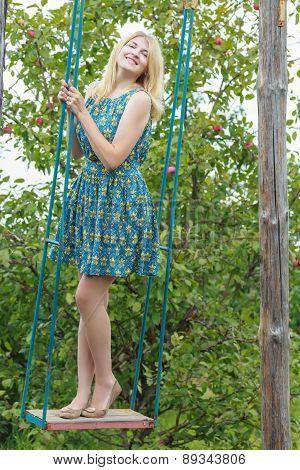 Fill Length Portrait Of Blonde Girl In Silk Sundress On Handmade Swing