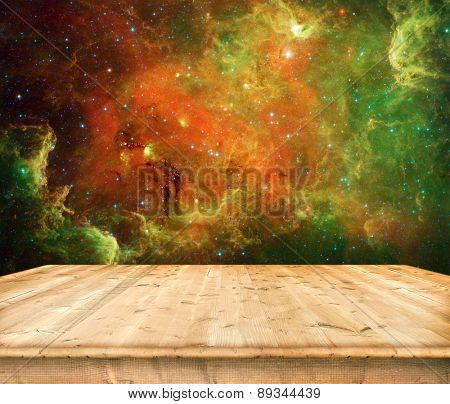 Empty wooden table on universe background. Elements of this image furnished by NASA
