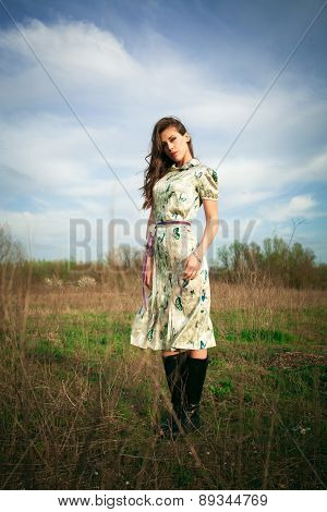 young woman in summer  dress stand in grass field, full body shot, look at camera