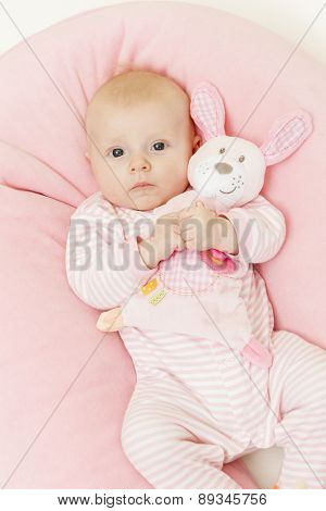 portrait of three months old baby girl holding a toy