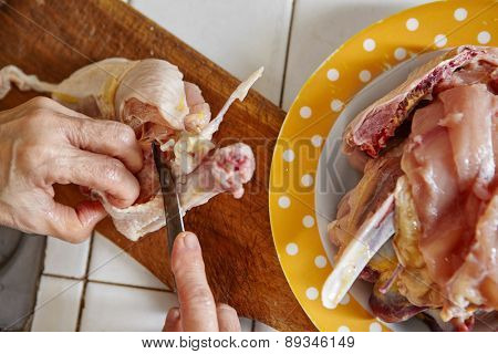 hand cutting raw chicken for the cooking