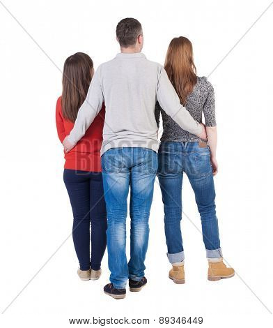 Back view of three friends  (woman and man).Two young girls hug the guy.  backside view of person.  Isolated over white background.