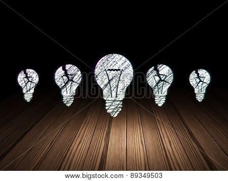 Finance concept: light bulb icon in grunge dark room
