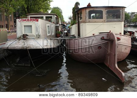 AMSTERDAM, NETHERLANDS - AUGUST 8, 2012: Two houseboats moored on the Amstel River near the Dutch National Opera in Amsterdam, Netherlands.