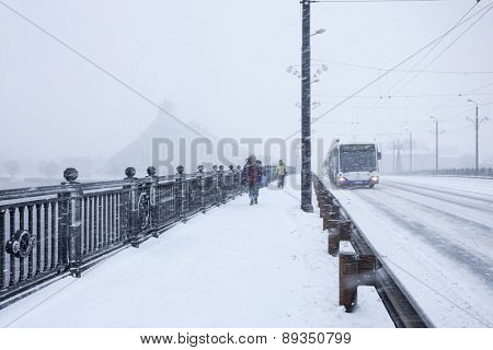 RIGA, LATVIA - DECEMBER 25, 2014: Unidentified Pedestrians and Bus with text RIGA on Stone bridge during heavy snow storm.