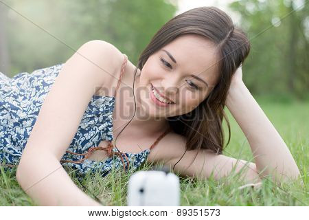 Beautiful asian smiling woman talking on cell phone outdoor