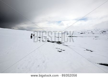ICELAND - MARCH 27, 2015: Tourists climb the mountain slopes during winter to view the scenic snow covered mountains, glacier and glacier lagoon at the Fjallsarlon Glacier in Iceland.