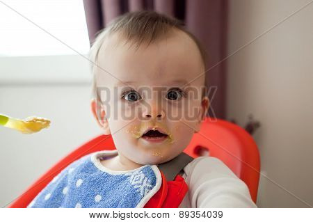 Surprised Baby Smeared With Food, Eats With His Mouth Open