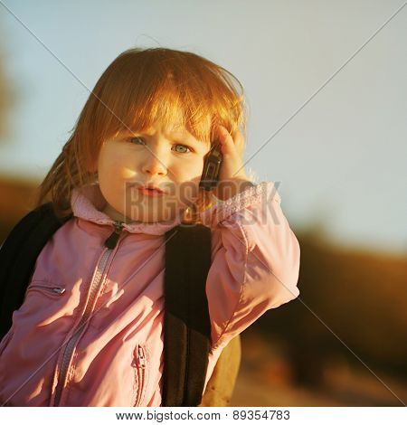 Little girl talking on the phone with a serious face