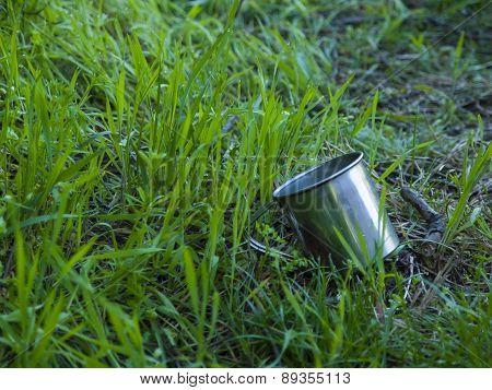 Metal Mug Lying On The Green Grass.