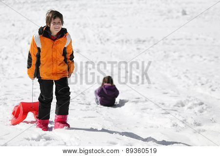 Little Boy Having Fun On The Red Sleigh In The Mountains In Winter
