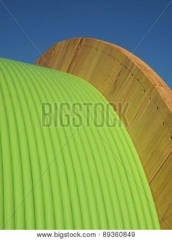 Green fiber optic cable on large wooden drum closeup