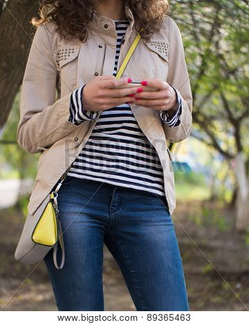 Girl Typing A Message On Her Phone In A Beige Jacket And Blue Jeans