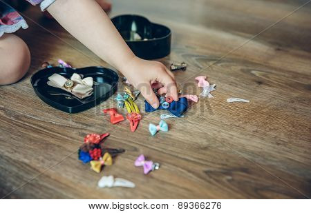 Baby girl hand playing with hair clips in the floor