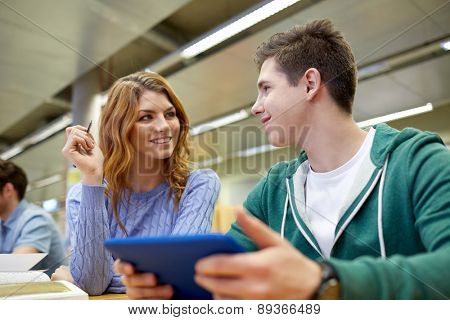 people, education, technology and school concept - happy students with tablet pc computer networking in library