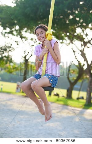 Young happy girl playing on the swing in the park at evening time