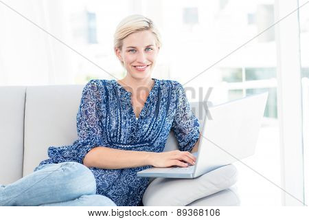 Pretty blonde woman using her laptop on the couch in the living room