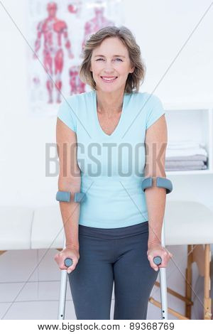 Woman standing with crutch and smiling at camera in medical office