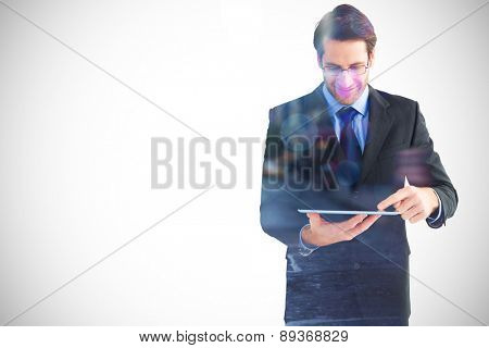 Businessman standing while using a tablet pc against blurry new york street