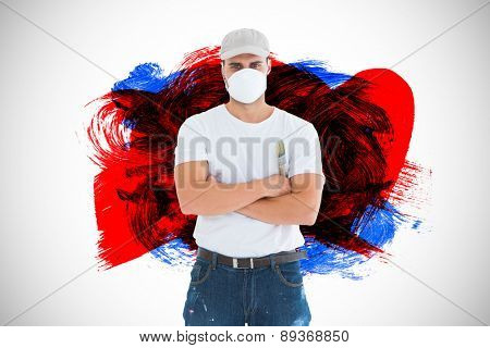 Man with paintbrush standing arms crossed by ladder against black red and blue paint