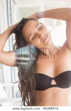 Beatiful woman in black bikini posing against wooden planks
